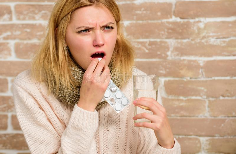 Pills for breaking fever. Headache and fever remedies. Woman tousled hair scarf hold glass water and tablets blister. Take medications to reduce fever. Girl stock photography