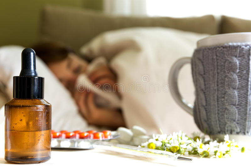 Pills, camomile tea and homeopathic extract on table. Young woman lying on a bed covered with blanket blowing her nose stock images