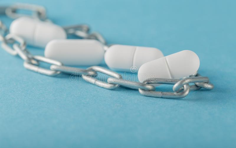 Pills on a colored background. Pill and chain on a colored background ,self-treatment concept royalty free stock images