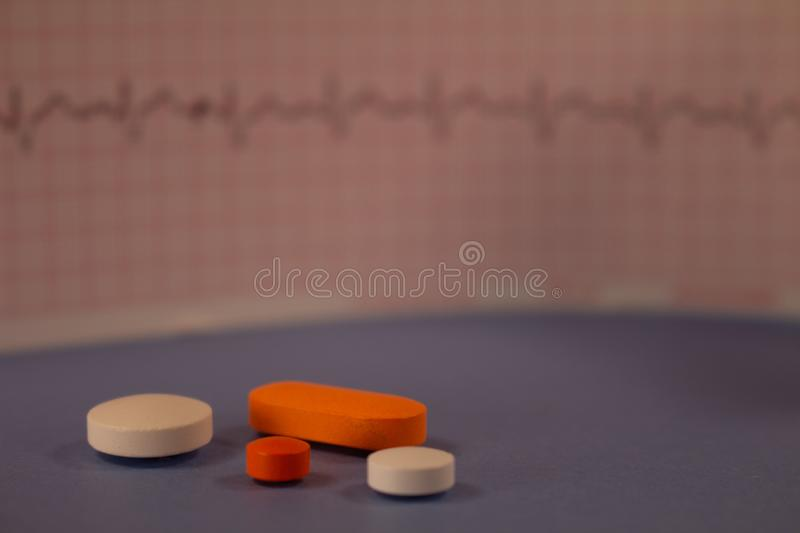 Pills of colors in a neutral background. Electrocardiogram strip out of focus stock images