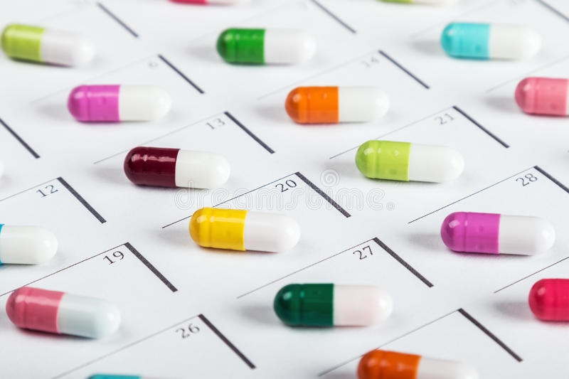 Pills are of different color on the calendar royalty free stock photo