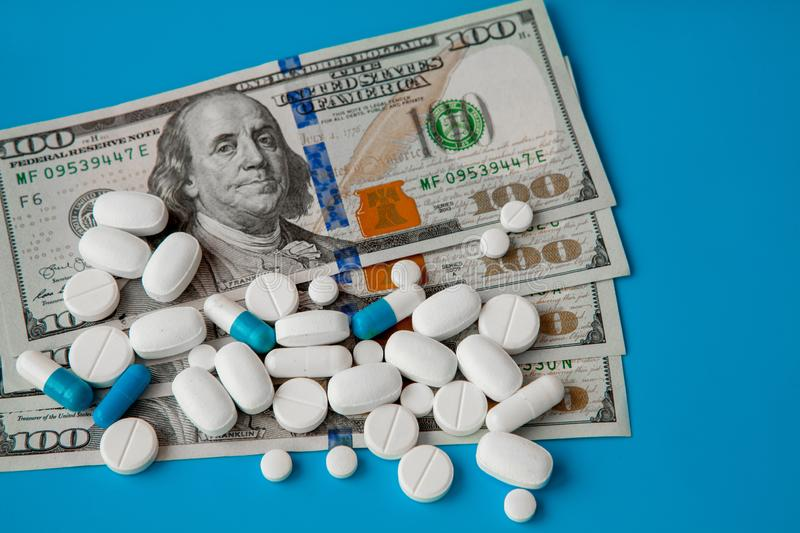 Pills on dollar money on blue background. Medicine expenses. High costs of medication concept. Close up.  stock photo