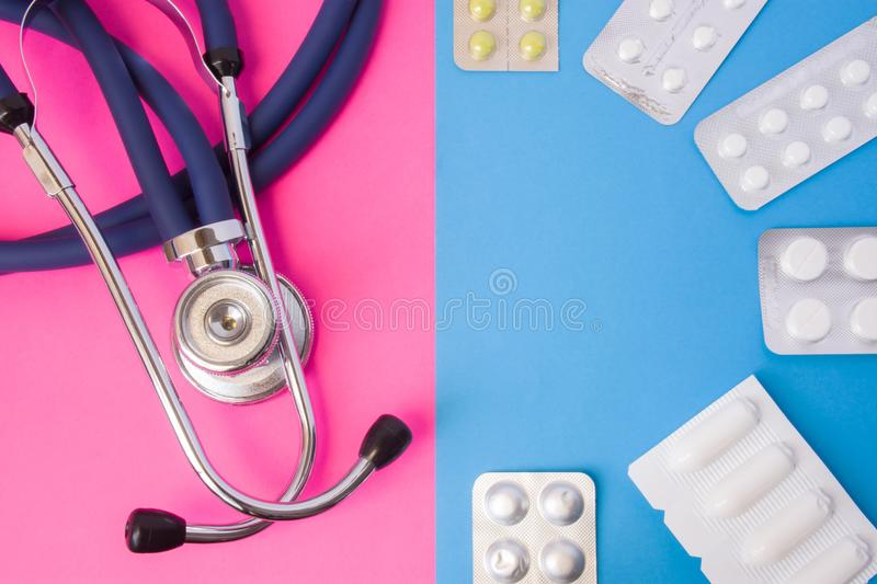 Pills, drugs, medictions and suppositories in blister package and medical stethoscope in two colors background: blue and pink. Con stock image