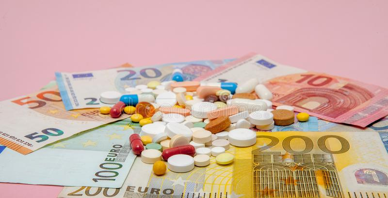 A pills and euro on a pink background with copy space. Soft focus. Concept of medicine, money and health.  stock image