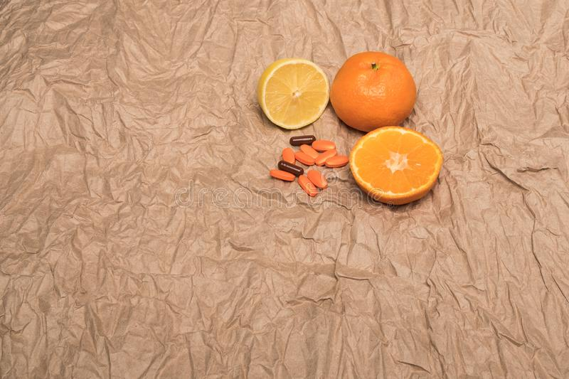Pills and fruits. Mandarins and orange pills. Crumpled paper background. Citrus fruit. royalty free stock image