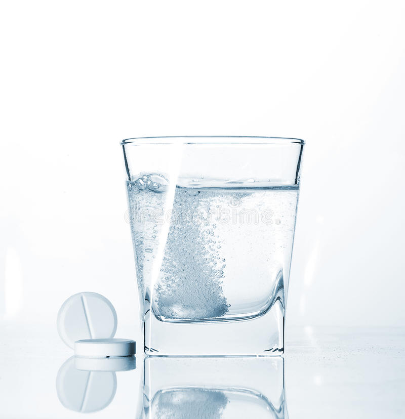Pills and glass of sparkling water stock photos