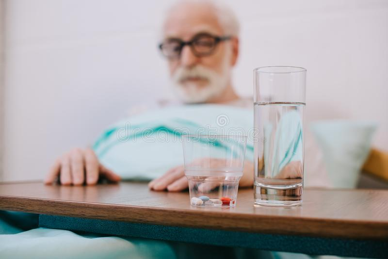 Pills and glass of water in front of senior man stock photos