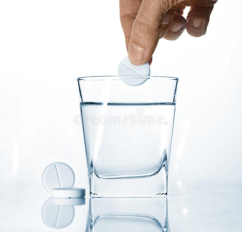 Pills and glass of water stock image