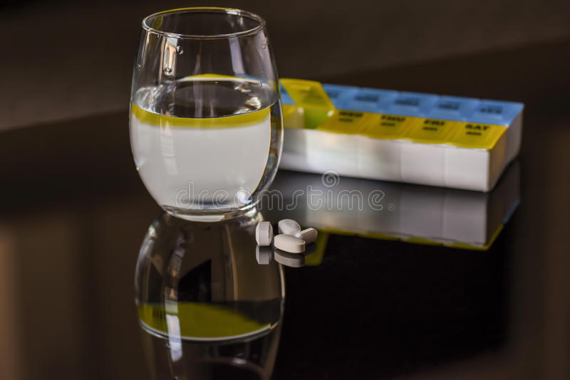 Pills and glass of water reflected in glossy black surface royalty free stock photos