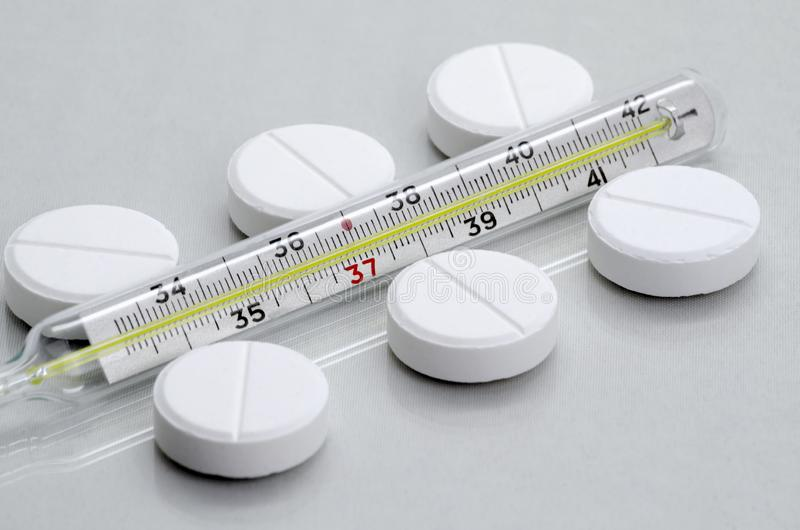 The pills lie next to the medical thermometer stock photo