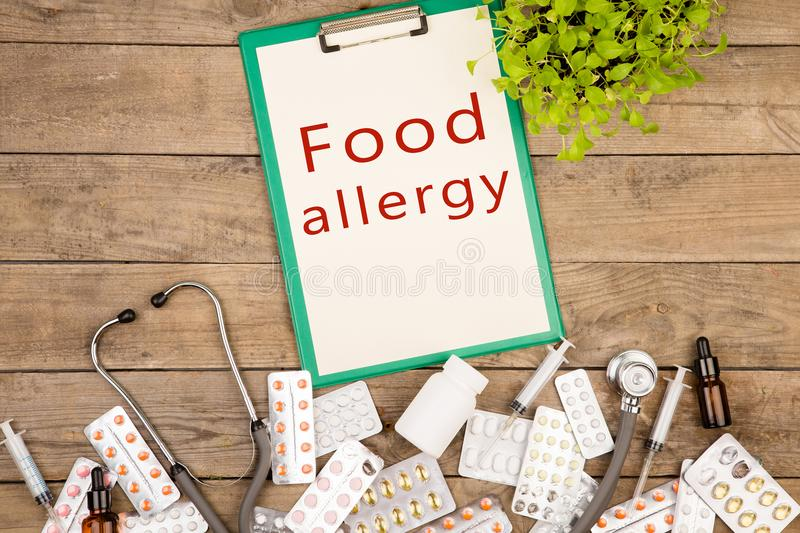 Pills, medical bottle, syringe, stethoscope and clipboard with clipboard with text & x22;Food allergy& x22;. On brown wooden table stock photos