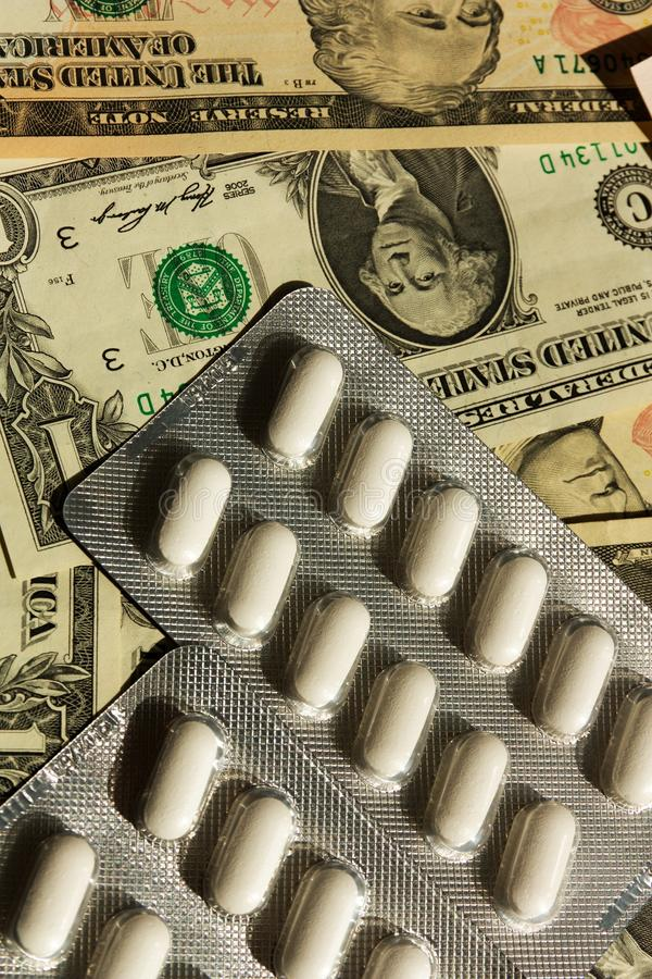 Pills and money. Health-care costs concept with pills on dollar bills, white pills and dollars stock image