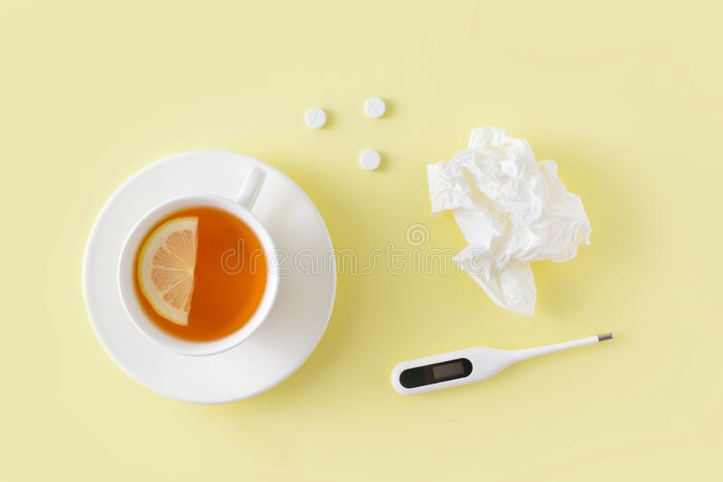 Pills, napkins for the nose, thermometer and cup of tea on yellow background. Cold and flu treatment set. Flat lay, top view. Pills, napkins for the nose royalty free stock photo