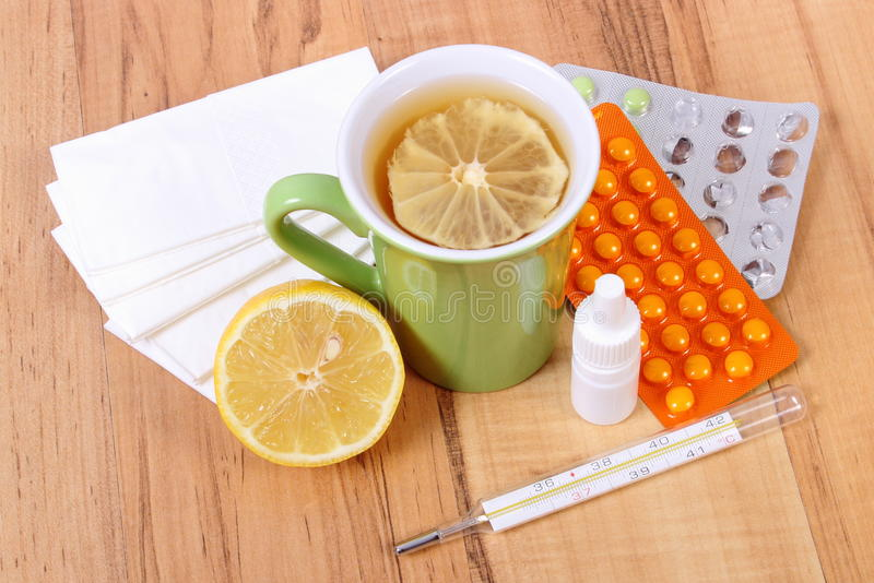 Pills and nose drops for colds, handkerchiefs and hot tea with lemon. Treatment of colds, flu and runny royalty free stock photo