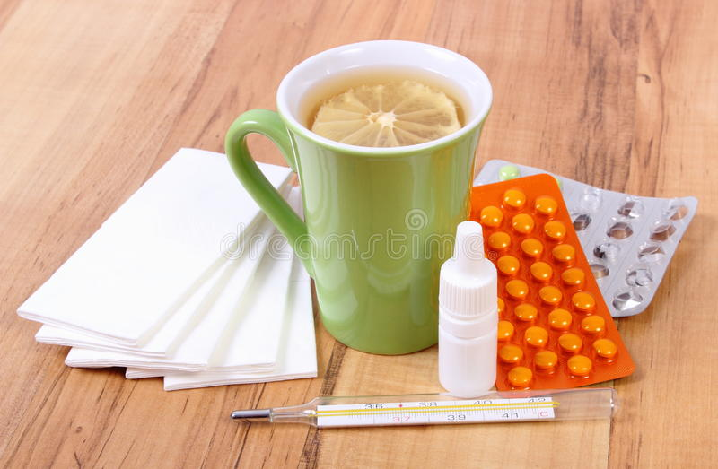Pills and nose drops for colds, handkerchiefs and hot tea with lemon. Treatment of colds, flu and runny stock photo