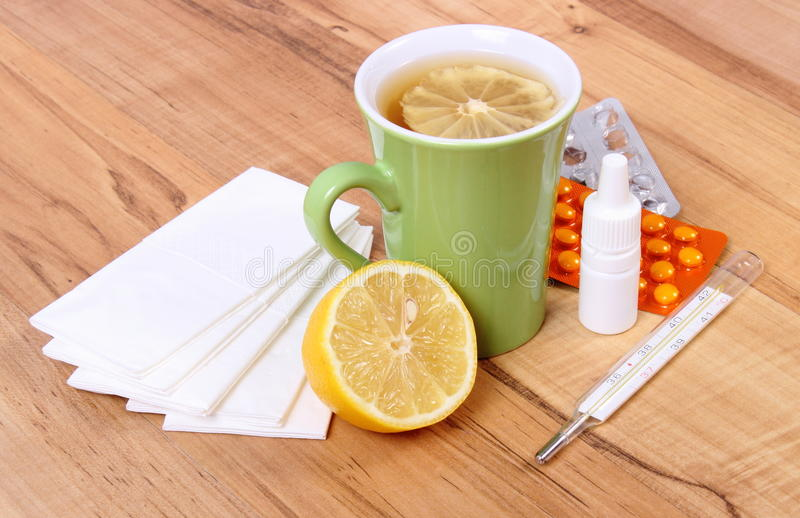 Pills and nose drops for colds, handkerchiefs and hot tea with lemon. Treatment of colds, flu and runny royalty free stock images