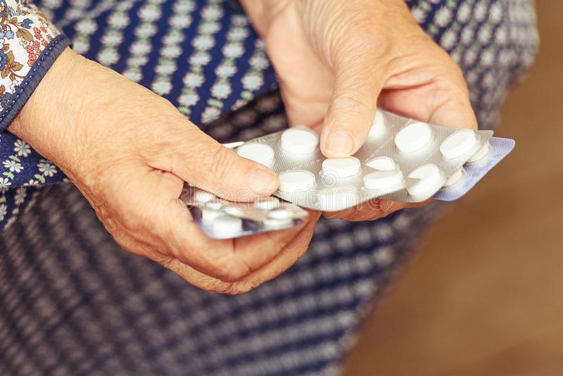 Pills in the hands of the old gum, toning. Pills, old age and the concept of health - pills in the hands of the old gum, toning royalty free stock image
