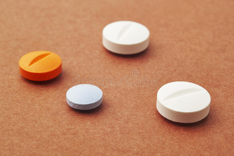 Pills over a brown background. Medicament treatment. Health care. Photo royalty free stock image