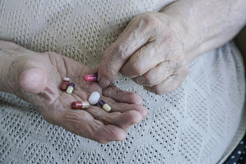 Pills on palm of a senior woman stock photo