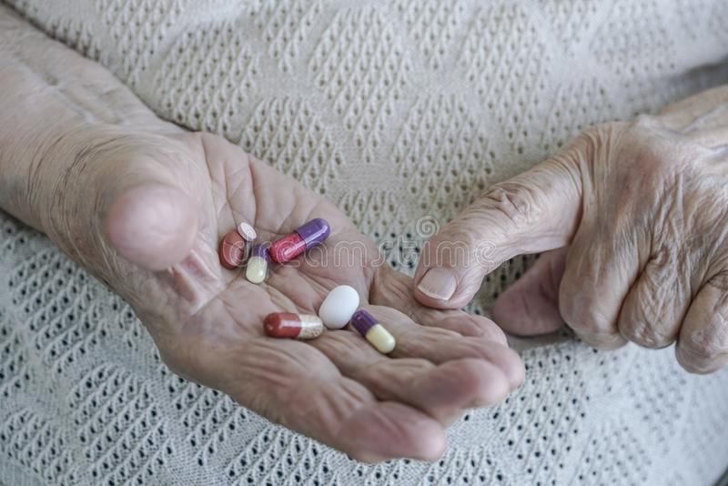 Pills on palm of a senior woman stock photos