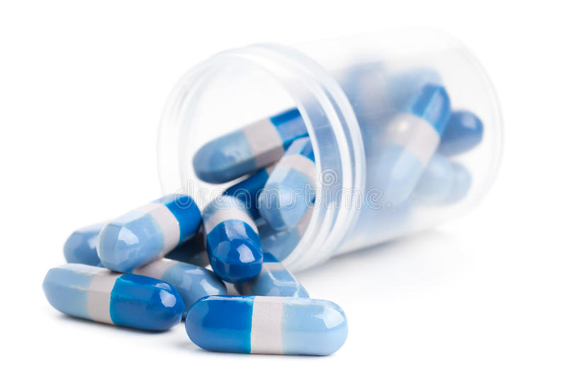 Pills in pill bottle. Blue pills in transparent pill bottle on white background royalty free stock photos