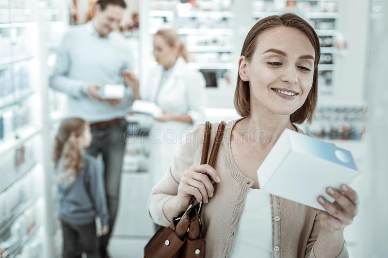 A spouse reading the pills prescription near the drugstore window. The pills prescription. A graceful spouse in high spirits carefully reading the pills royalty free stock image