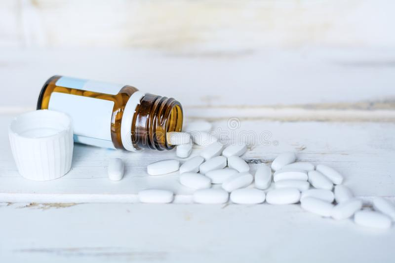 Pills in a Small Bottle. Blisters with pills on a white wooden background stock photography