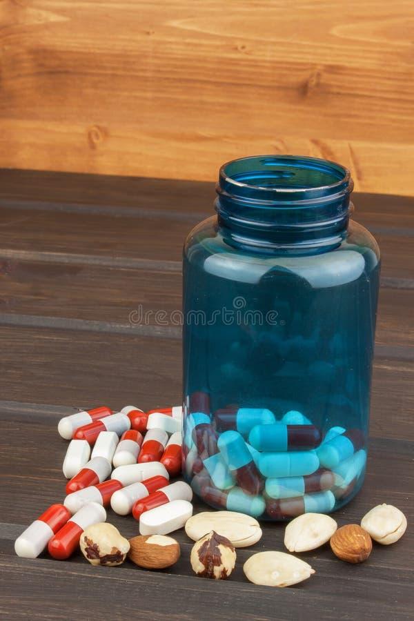 Pills som spiller från en öppen flaska dopa sporten Missbruk av anabola steroider för sportar arkivbilder