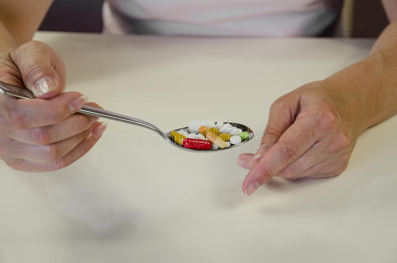 Pills on spoon. Human hand with spoon full of colorful medicals stock image