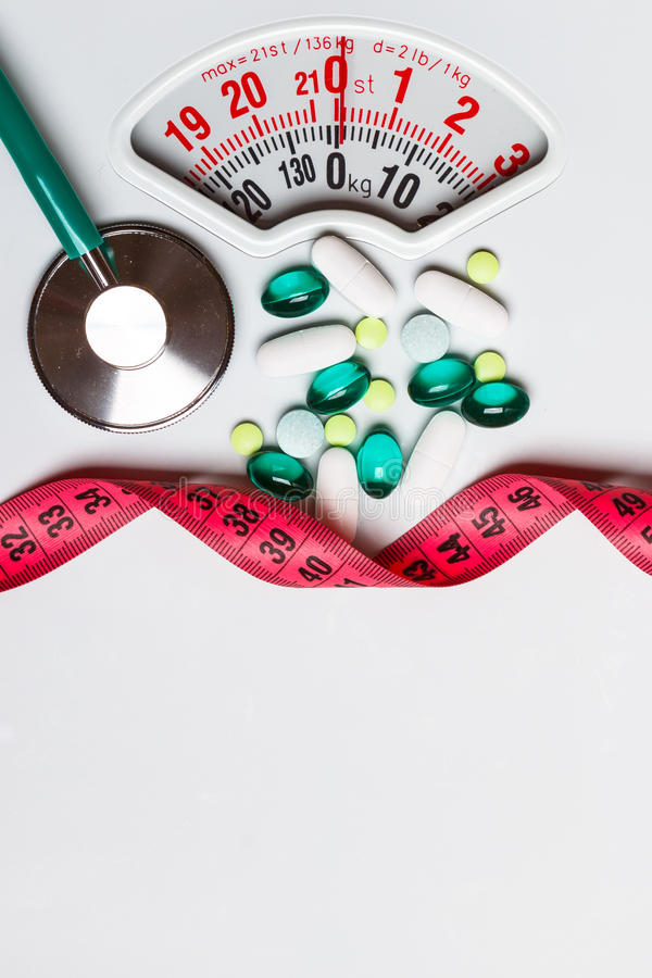 Pills stethoscope measuring tape on scales. Health care. Healthy eating, medicine, health care, food supplements and weight loss concept. Pills with measuring royalty free stock photography
