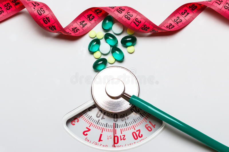 Pills stethoscope measuring tape on scales. Health care. Healthy eating, medicine, health care, food supplements and weight loss concept. Pills with measuring stock photography