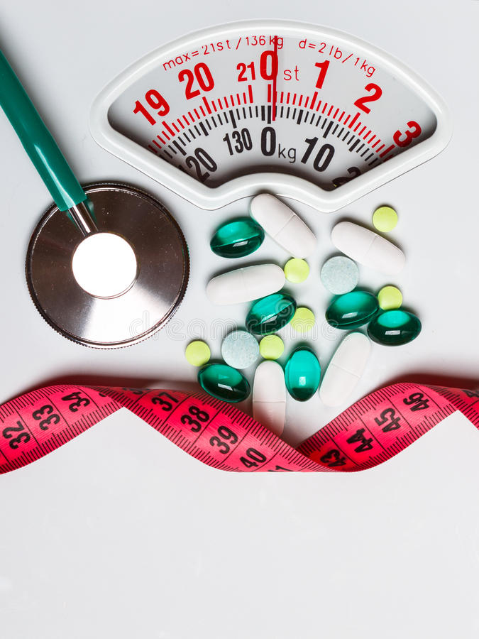 Pills stethoscope measuring tape on scales. Health care. Healthy eating, medicine, health care, food supplements and weight loss concept. Pills with measuring royalty free stock images