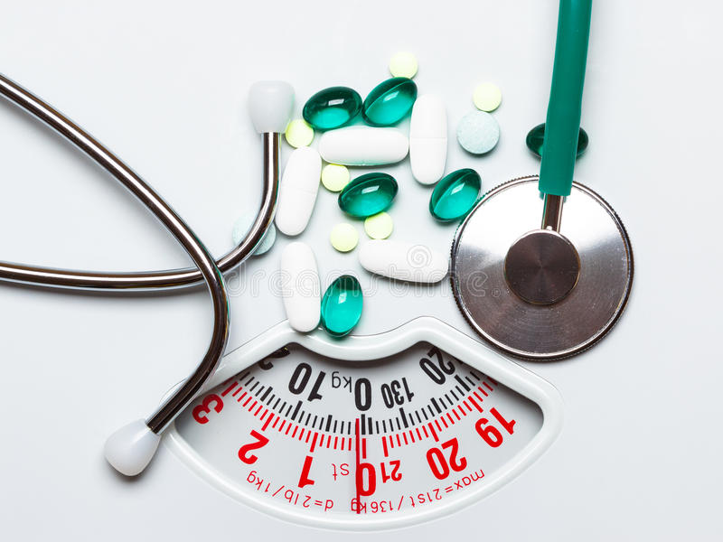 Pills and stethoscope on scales. Health care. Healthy eating, medicine, health care, food supplements and weight loss concept. Pills with stethoscope on white royalty free stock photography