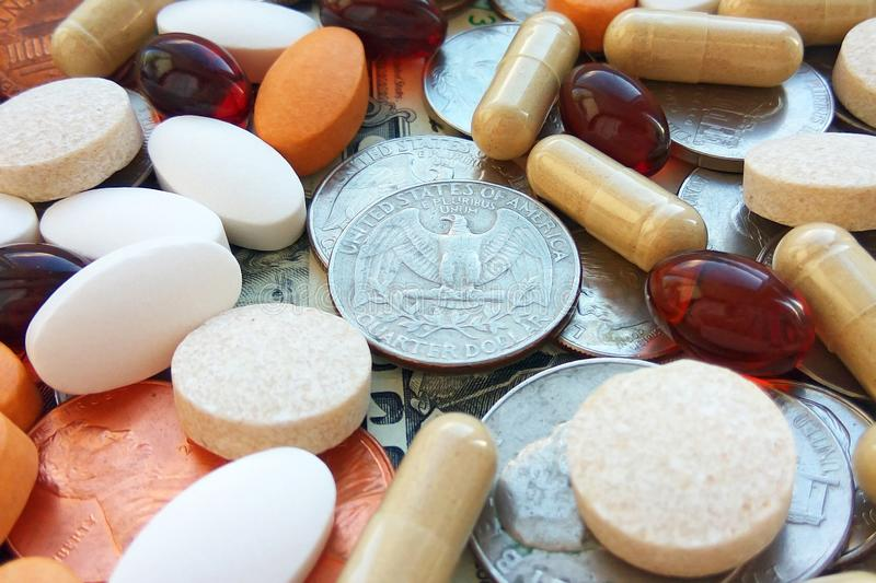 Pills, tablets and capsules with American coins on dollar usa background. Pharmacy and money theme, health care, drug prescription for treatment medication royalty free stock photo