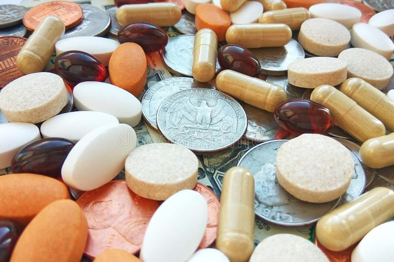Pills, tablets and capsules with American coins on dollar usa background. Pharmacy and money theme, health care, drug prescription for treatment medication stock photos