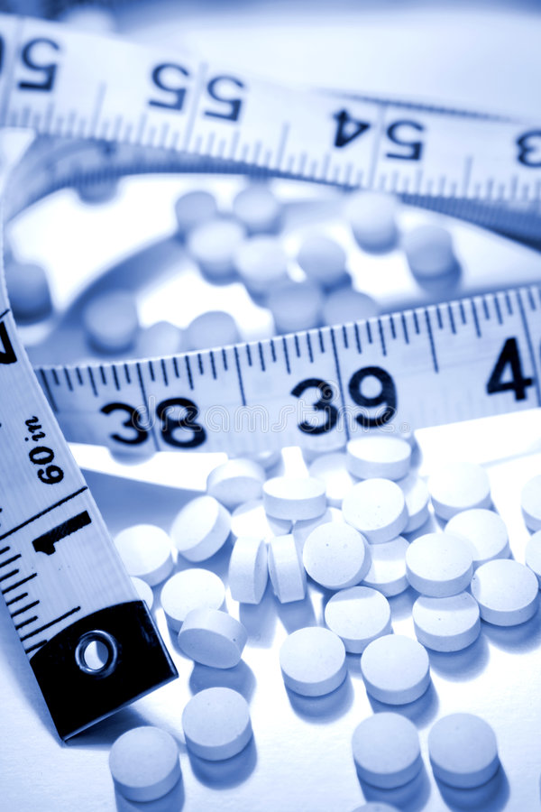 pills and tape measure royalty free stock photo