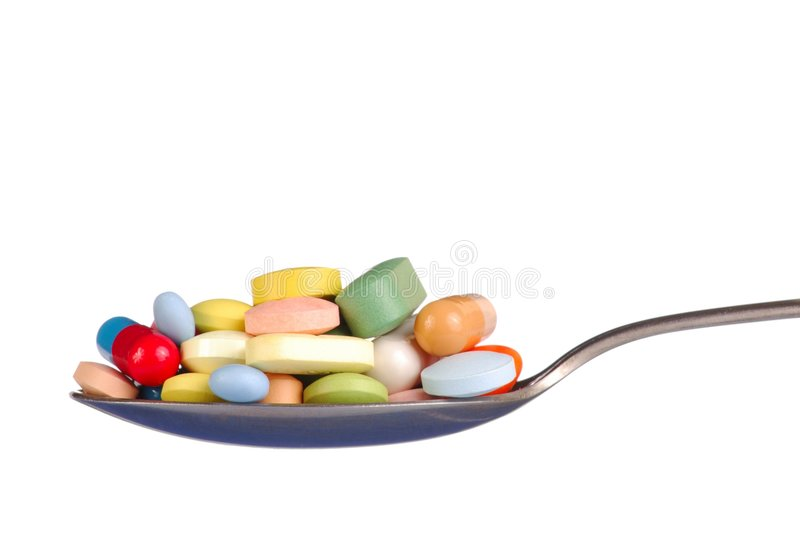 Pills on Teaspoon. Macro of pills and capsules on a teaspoon stock photography