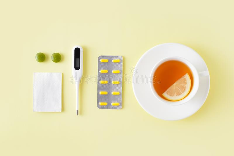 Pills, thermometer and cup of tea on yellow background. Cold and flu treatment set. Flat lay, top view. Free copy space. Pills, thermometer and cup of tea on royalty free stock photos