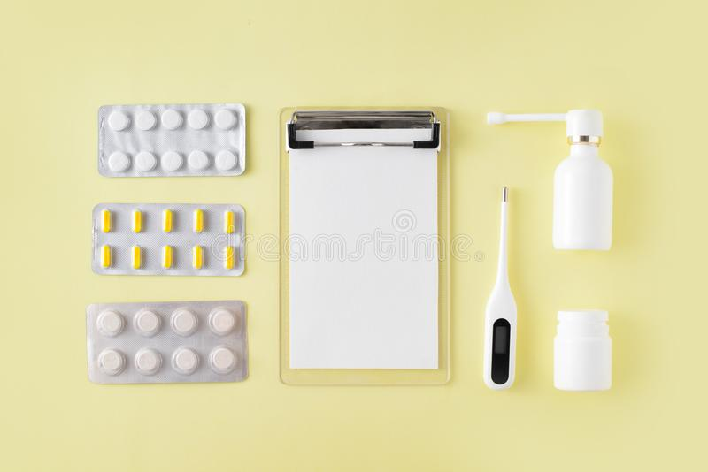 Pills, thermometer and note for recipe on yellow background. Cold and flu treatment set. Flat lay, top view. Pills, thermometer and note for recipe on yellow royalty free stock photos