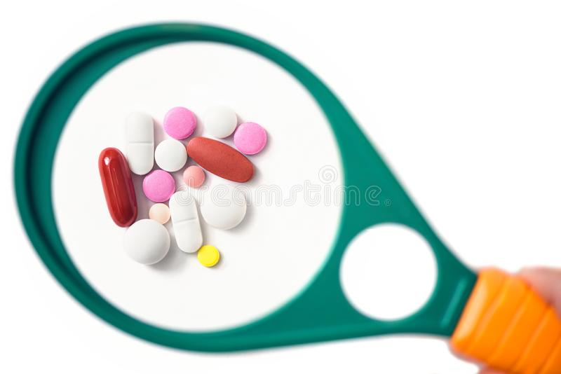 Pills under a magnifying glass on the white background. Testing, verification and determining pharmaceutical counterfeiting or fake stock photo