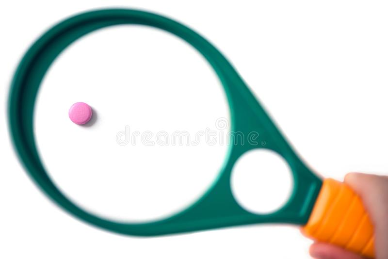 One pill under a magnifying glass on the white background. Pills under a magnifying glass on the white background. Testing, verification and determining stock photography