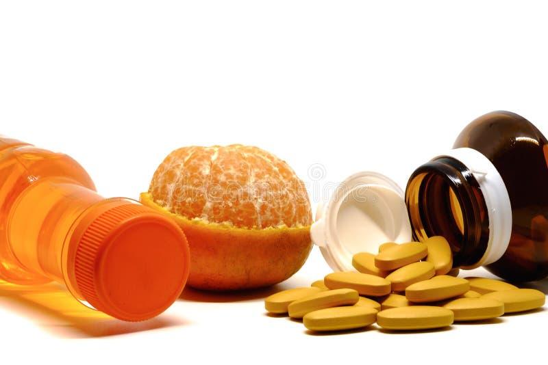 Pills of vitamin C, fresh orange fruit, and sweet drinking bottle on white background stock photo