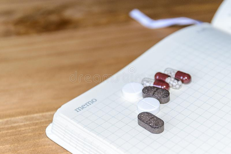 Pills and a white sheet of paper for copy space on wooden background. The view from the top. The concept of minimalism medicine stock photo