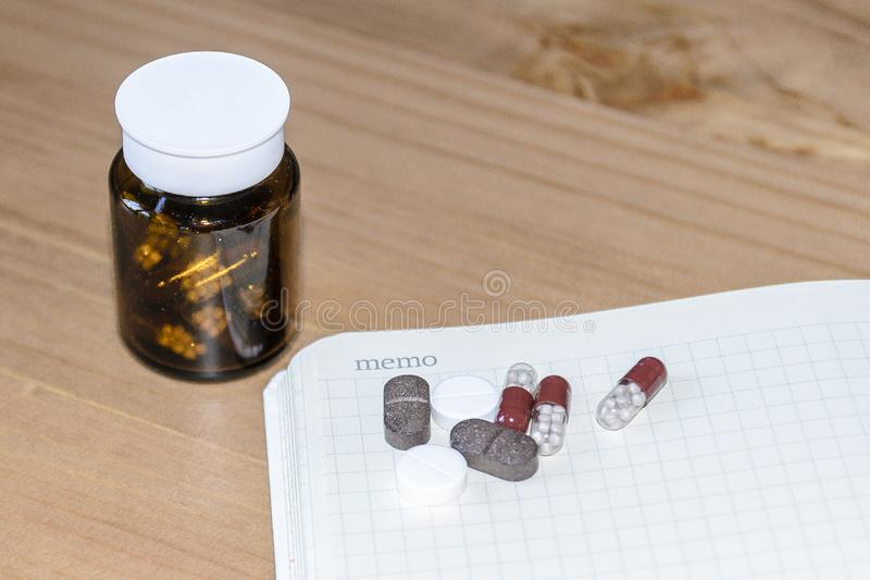 A Pills and a white sheet of paper for copy space on wooden background. The view from the top. The concept of minimalism medicine. Pills and a white sheet of royalty free stock images