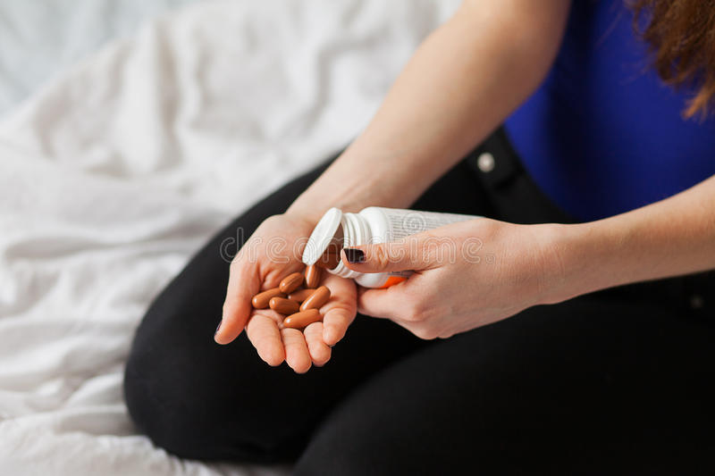 Pills in a white woman hands stock images