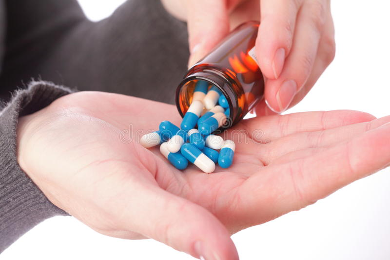 Pills in woman hand stock photography