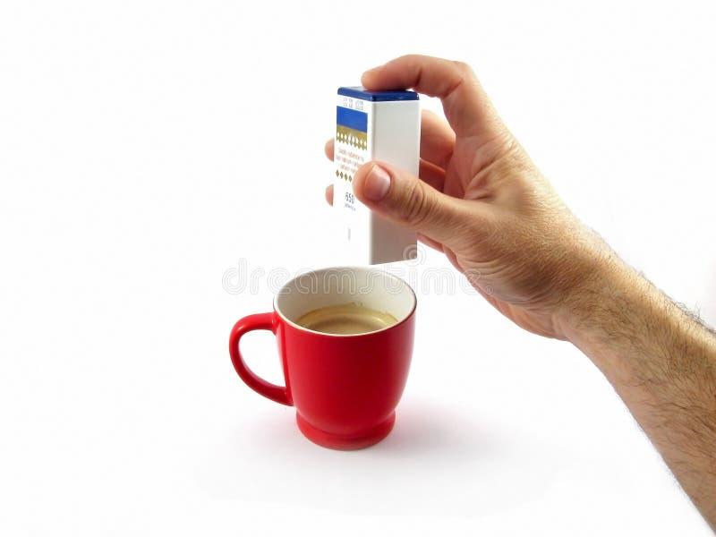 Pillule de sucre de diabète mettant dans la cuvette de café photos libres de droits