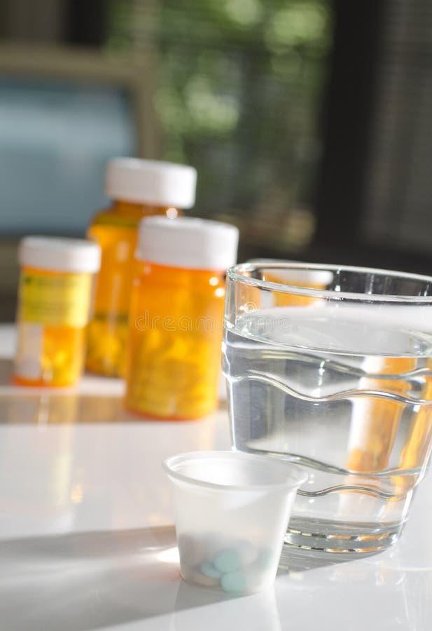 Pillules dans la cuvette de médecine avec la glace d'eau photos libres de droits