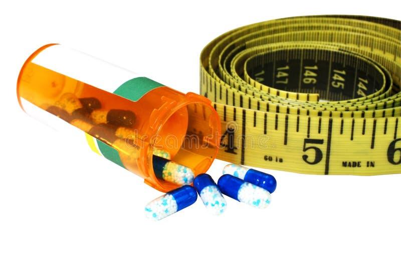 Pillules de régime avec la bande de mesure photos stock