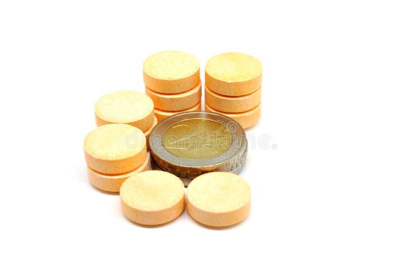 Pillules de vitamine de C et euro pièces de monnaie image libre de droits